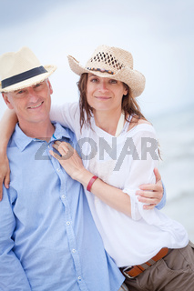 happy adult couple in summertime on beach