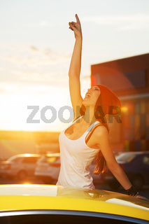Happy fashion woman standing at the car