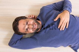 Happy man lying on floor