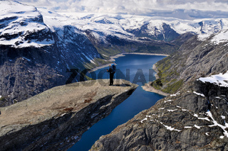 Backpacker standing on the sunlit Trolltunga rock