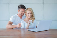 Couple drinking coffee and reading on a laptop