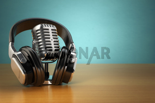 Vintage microphone and headphones on green background. Concept audio and studio recording.