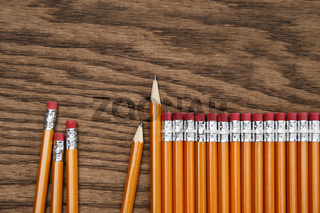 A row of red pencils on wood surface