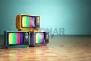 Vintage television concept. Stack of retro tv set on green background.