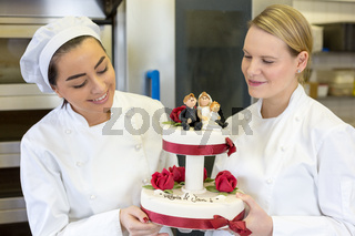 Confectioners or bakers presenting wedding cake