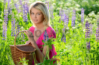 The beautiful woman in the field with lupin
