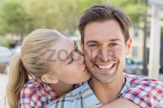 Young hip woman giving boyfriend kiss on the cheek
