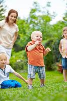 Baby beim Laufen lernen im Kreis der Familie