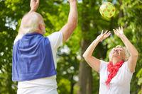 Alte Frau und Senior spielen Ball im Park