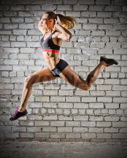 Muscular jumping woman on grey brick wall background (normal version)