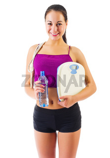 Sporty young girl with skipping rope and scales isolated