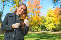 Blond Woman in Gray Coat Holding Dry Leaves