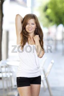 Laechelnde junge Frau in der Stadt