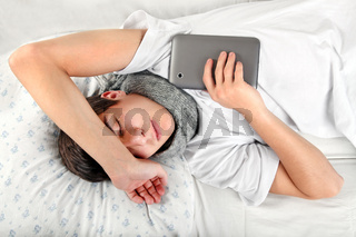 Young Man sleeps with Tablet Computer