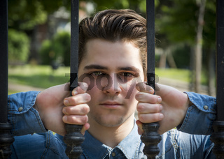 Attractive young man behind metal gate