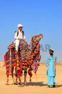 Local man riding a camel at Desert Festival, Jaisalmer, India