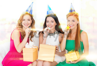 three women wearing hats with gifts blowing horns