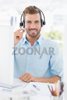 Portrait of a casual young man with headset using computer