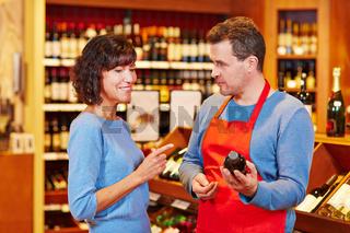 Verkäufer im Supermarkt empfiehlt eine Flasche Wein