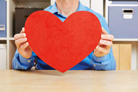 Mann hält großes rotes Herz