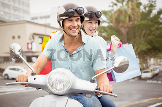 Hip young couple riding scooter with shopping bags