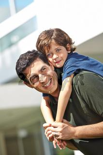 Glücklicher Vater trägt Sohn huckepack