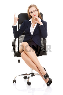 Beautiful caucasian business woman sitting on a chair and advertising.