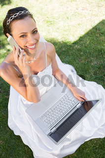 Happy bride with laptop using cellphone on grass