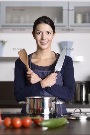 Lächelnde Hausfrau steht in der Küche mit Messer u