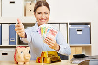 Frau mit Geld und Gold hält Daumen hoch