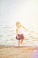 Mädchen spielt am Strand im Sommer