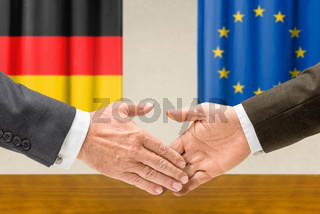 Representatives of Germany and the EU shake hands