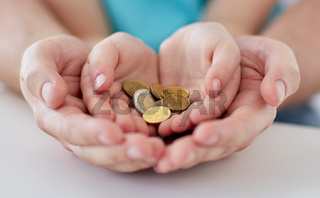 close up of family hands holding euro money coins