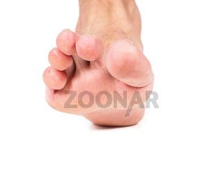 Pointing barefoot towards white