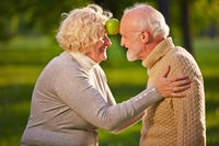 Paar Senioren balanciert Apfel zwischen Stirn