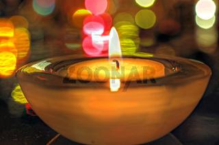 brennende Kerze und bunte Lichter