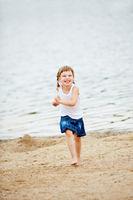 Lachendes Mädchen läuft am Strand