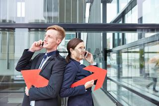 Zwei Geschäftsleute mit Pfeil telefonieren mit Smartphone