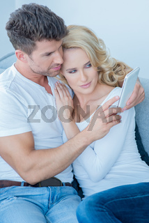 Loving couple reading an sms on a mobile phone