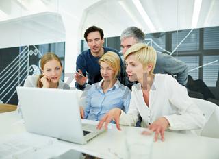 Team im Büro schaut auf Bildschirm von Laptop