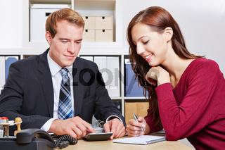 Steuerberater spricht mit Klientin im Büro