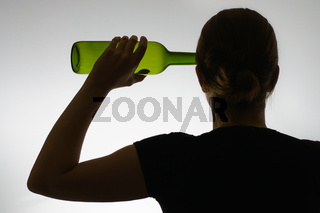 Backside view of a woman's silhouette with a wine bottle