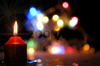 rote brennende Kerze mit bunten Lichtern