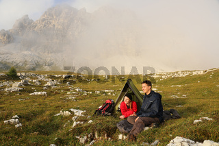 Junge Leute zelten im Nebel in den Bergen