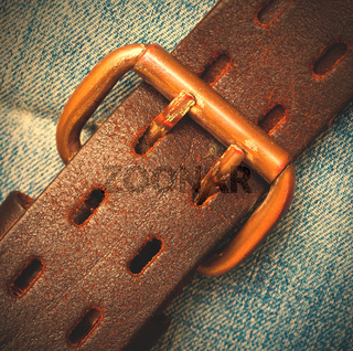 clasped leather belt on jeans background