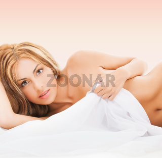 beautiful naked woman lying and covering herself