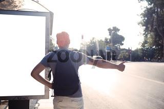 Man standing near bus stop thumbing a lift