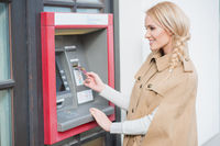 Pretty blond woman drawing money at an ATM