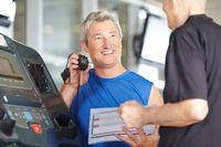 Fitnesstrainer mit Stoppuhr bei Senior am Laufband
