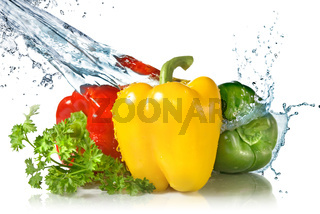 red, yellow, green pepper and parsley with water splash isolated on white